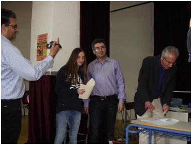 """Ο κ. Φυντίκογλου, καθηγητής της Φιλοσοφικής του ΑΠΘ επιδίδει το 1ο Βραβείο καλύτερης  Ομιλήτριας και μέλος της νικήτριας ομάδας """"Τα παιδιά του Περικλή"""" στην Αφροδίτη Καράταγλη."""